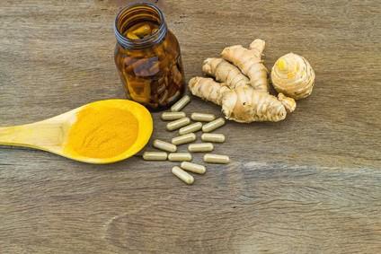 Braunes Arzneimittel Glas mit Kurkuma Kapseln, Kurkuma Gewürzpulver auf einem Holzlöffel und Kurkuma Wurzel Rhizom